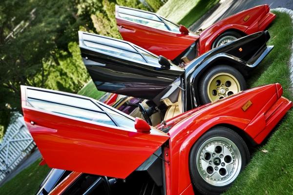 Un Lamborghini negro entre dos rojos