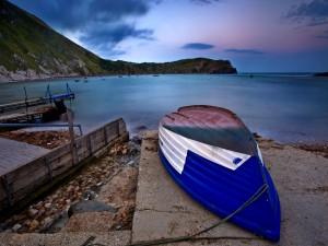 Barca dada la vuelta en la orilla del lago