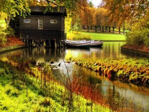 Postal: Barcas en el río junto a la cabaña de madera