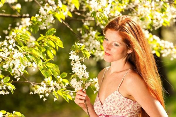 Joven sosteniendo una rama con flores