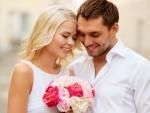 Feliz pareja admirando un ramo de novia