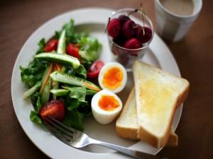 Huevo cocido con ensalada y cerezas para el desayuno