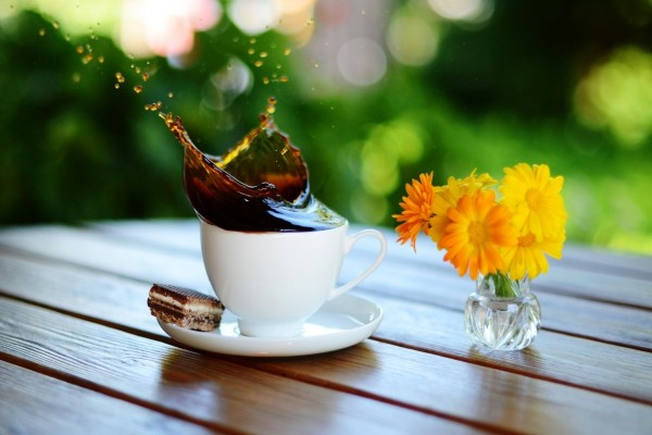 Café en movimiento y un pequeño jarrón con flores