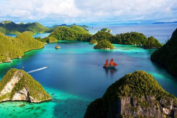 Barco con velas rojas entre los islotes