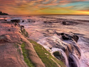 Postal: Mar y rocas iluminados por los primeros rayos del sol