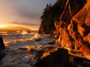 El sol iluminando el agua del mar y las rocas