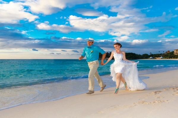 Pareja de recién casados corriendo en la playa