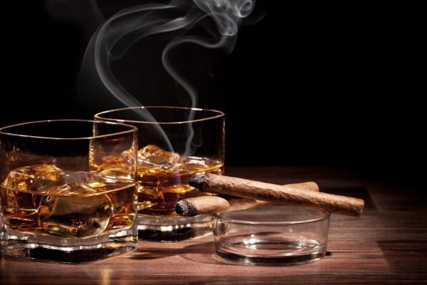 Vasos de whisky con hielo y unos puros