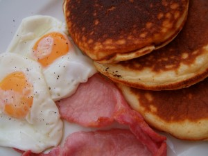 Buen desayuno con huevos, lomo y tortitas