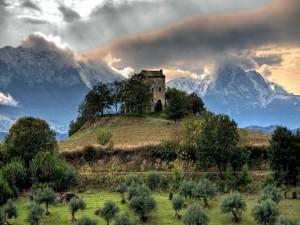 Grandes montañas tras la casa de piedra