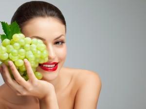 Bella mujer con un racimo de uvas verdes