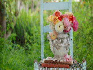 Postal: Jarrón con flores y unos libros sobre una silla