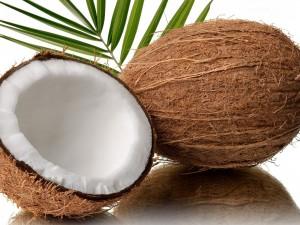 Un coco recién cortado y otro entero