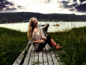 Postal: Una joven sentada en el camino de madera