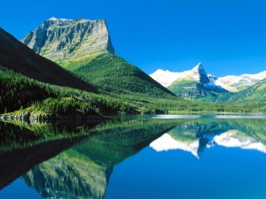 Montañas y pinos verdes reflejados en el lago