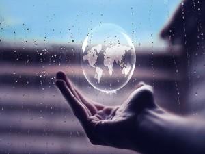 Postal: Globo terráqueo flotando sobre la palma de la mano