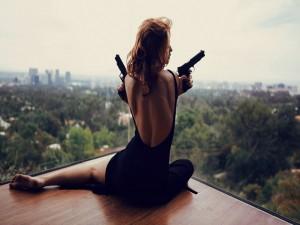 Postal: Modelo con una pistola en cada mano