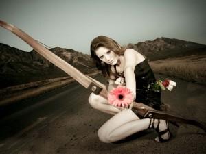 Una modelo disparando flores con el arco