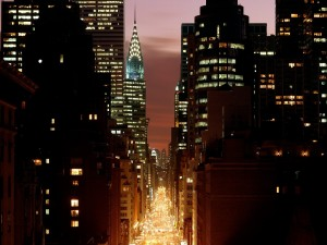 Postal: Calle iluminada entre los edificios de Nueva York
