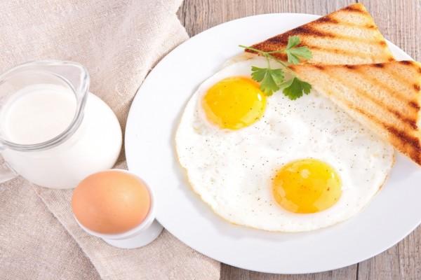 Rico desayuno con pan, huevos y leche