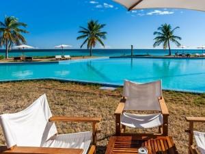 Postal: Tumbonas y sombrillas junto a una piscina
