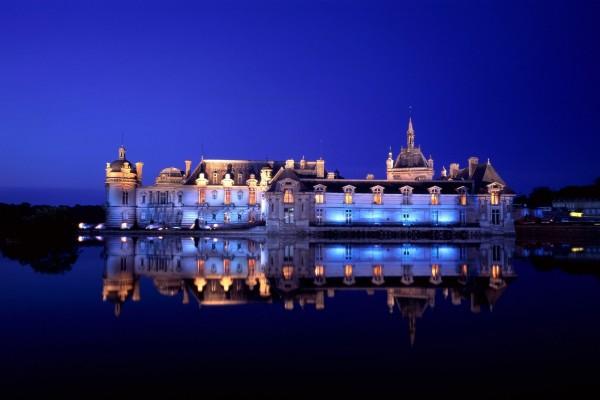 Un castillo reflejado en el agua durante la noche