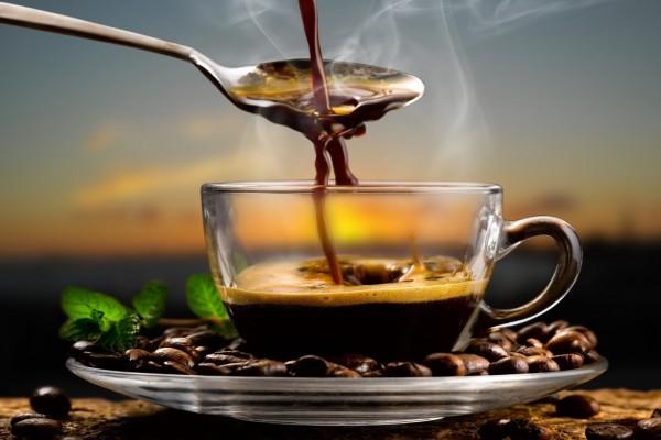 Cuchara y taza con café humeante