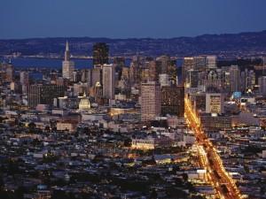 Postal: Vista de la ciudad iluminada al anochecer