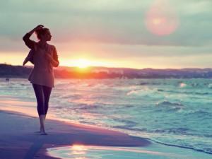 Mujer paseando por la playa a la salida del sol