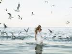 Mujer en el mar junto a las gaviotas