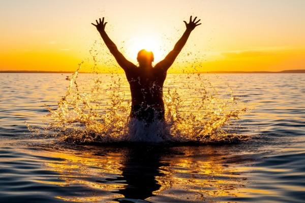 Saltando en el mar frente a los últimos rayos de sol