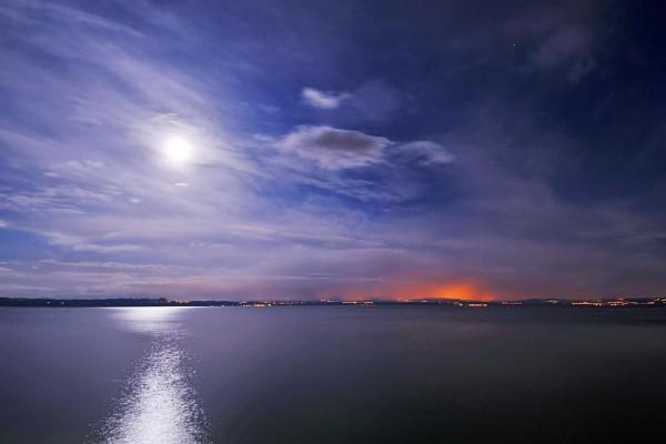 La luna entre las nubes iluminando el agua