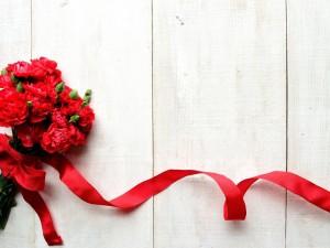 Ramo de claveles con una cinta roja
