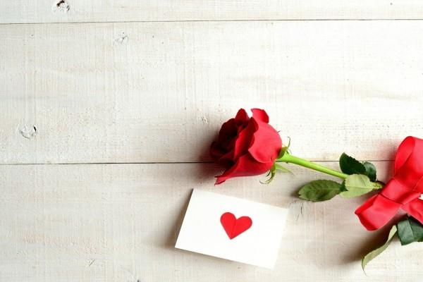 Rosa con cinta roja y una carta de amor