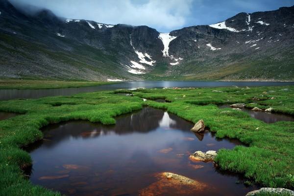 Un lago con piedras y hierba junto a la montaña