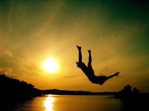 Un joven saltando al agua al atardecer