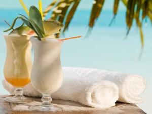 Cócteles con frutas tropicales y toallas para el mar