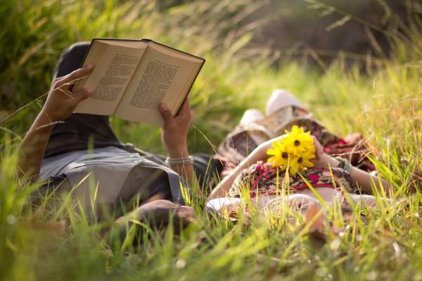 Pareja leyendo sobre la hierba
