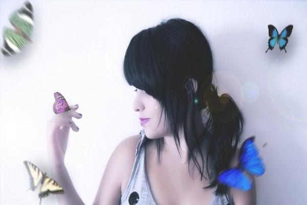 Mariposa posada en la mano de una mujer