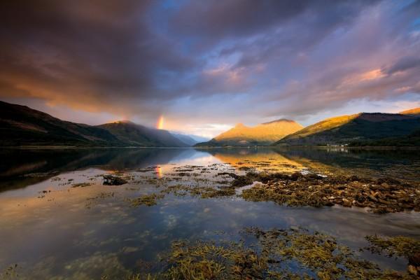 Arco iris entre nubes y montañas de Escocia