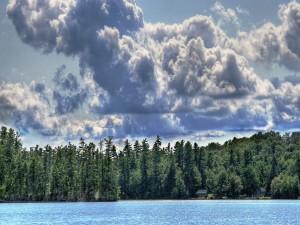 Grandes nubes sobre el lago y los pinos