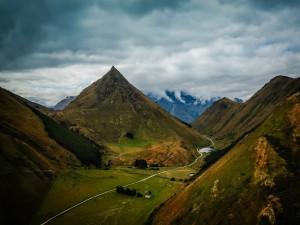 Postal: Un camino y un lago entre las montañas