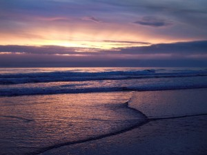 Olas llegando a la playa en un bello atardecer