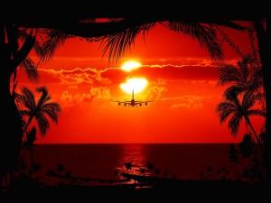 Avión atravesando el mar frente al ocaso del sol