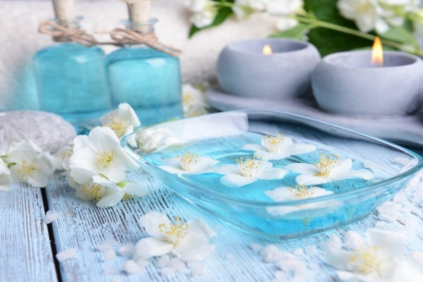 Velas y flores sobre el agua azul