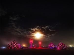 Gente admirando el arte con luces al anochecer