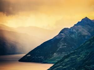 Postal: Un cielo dorado sobre el lago y las montañas
