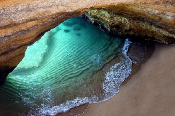 Arco en la playa sobre la arena y el agua