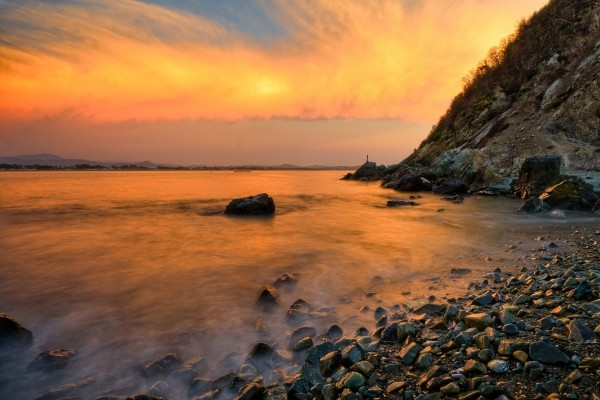 Un bonito atardecer visto desde la orilla pedregosa