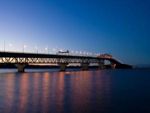 Largo puente iluminado al caer la noche